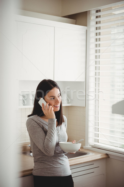 Woman talking on smart phone while holding food bowl Stock photo © wavebreak_media