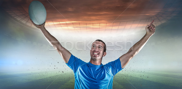 Composite image of happy rugby player in blue jersey holding ball with arms raised Stock photo © wavebreak_media