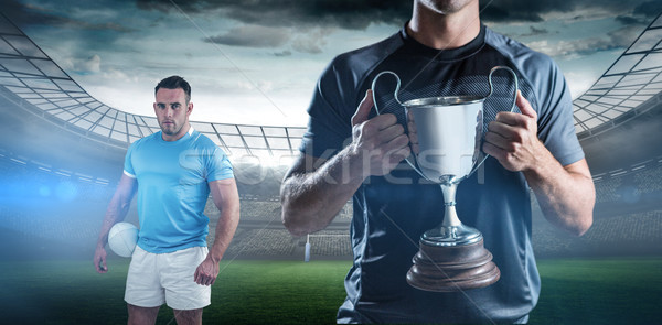 Composite image of victorious rugby player holding trophy Stock photo © wavebreak_media
