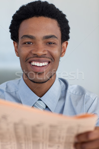 Afro-American businessman with a newspaper smiling at the camera Stock photo © wavebreak_media