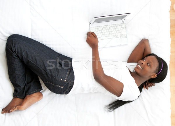 Happy woman surfing the internet lying on a bed Stock photo © wavebreak_media