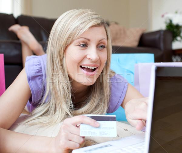Happy woman shopping online lying on the floor  Stock photo © wavebreak_media