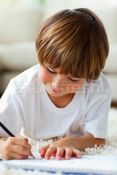 Jolly little boy drawing lying on the floor Stock photo © wavebreak_media
