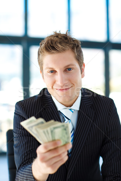 Junior businessman holding dollars and looking to the camera Stock photo © wavebreak_media