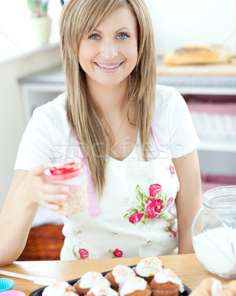 Attractive woman showing cakes in the kitchen  Stock photo © wavebreak_media