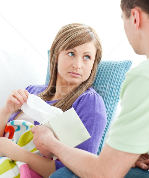 Assertive man giving his ill girlfriend tissue lying on a sofa Stock photo © wavebreak_media