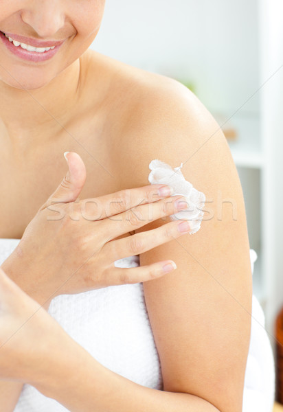 Happy young woman with a towel putting cream on her face in the bathroom at home Stock photo © wavebreak_media