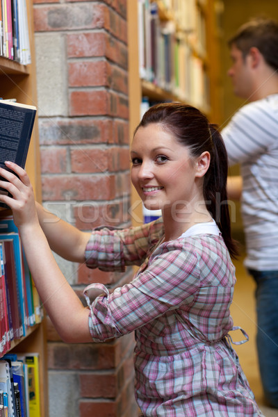 Charming young woman looking for a book in a bookstore Stock photo © wavebreak_media