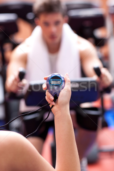 Woman holding a chronometer and man doing physical exercise Stock photo © wavebreak_media