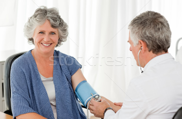 A senior doctor taking the blood pressure of his patient in his office Stock photo © wavebreak_media