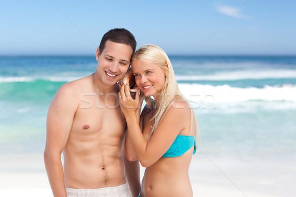 Pár hallgat kagyló kezek boldog tenger Stock fotó © wavebreak_media