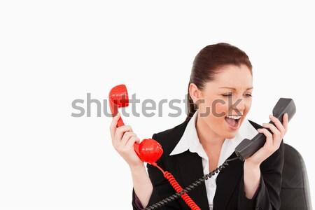 Stock photo: Cute secretary driven crazy by the phone calls against a white background