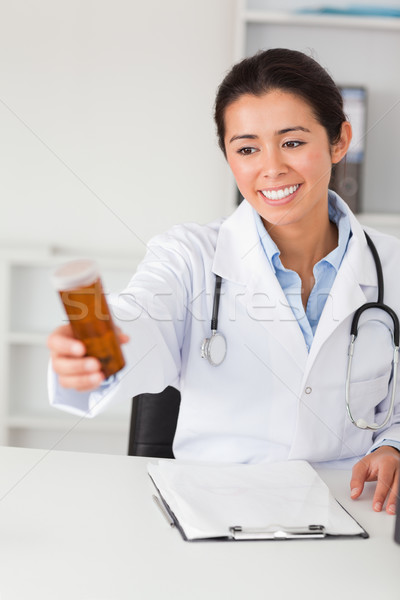 Lovely smiling doctor holding a box of pills while sitting in her office Stock photo © wavebreak_media