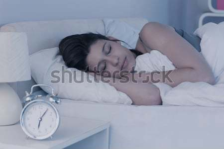 Tired woman hidding her head in a pillow while the alarmclock is ringing in her bedroom Stock photo © wavebreak_media