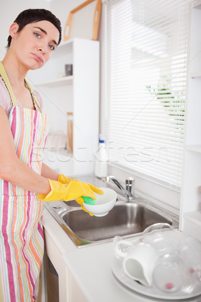 Sad woman washing the dishes in the kitchen Stock photo © wavebreak_media