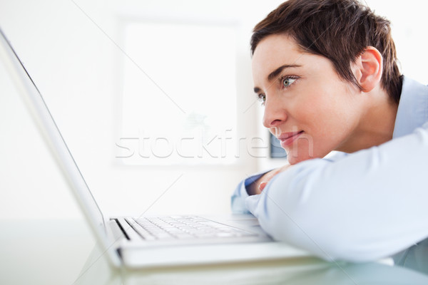Brunette short-haired businesswoman with a laptop in an office Stock photo © wavebreak_media