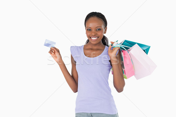 Happy smiling woman with her shopping and credit card on white background Stock photo © wavebreak_media