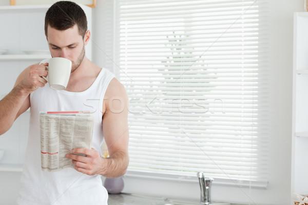 Homme potable thé lecture nouvelles cuisine Photo stock © wavebreak_media