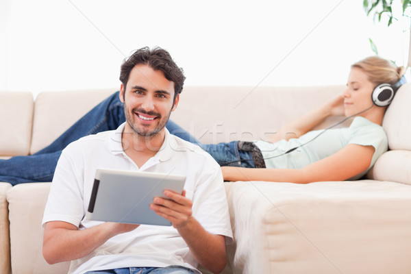 Man using a tablet computer while his wife is listening to music in their living room Stock photo © wavebreak_media