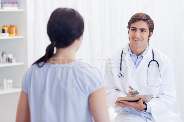 Uśmiechnięty młodych lekarz mówić pacjenta lekarza Zdjęcia stock © wavebreak_media