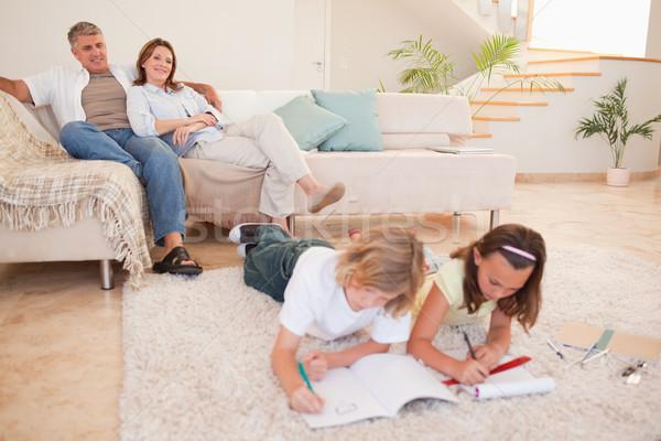 Children doing homework with their parents behind them Stock photo © wavebreak_media