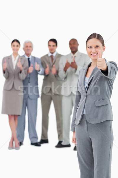 Saleswoman with thumb up and her team behind her against a white background Stock photo © wavebreak_media