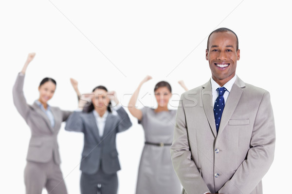 Close-up of a happy businessman smiling with enthusiastic co-workers raising their arms in the backg Stock photo © wavebreak_media