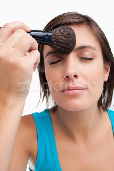 Calm teenage closing her eyes while applying powder Stock photo © wavebreak_media