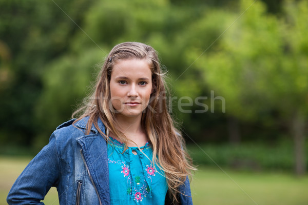Teenager standing upright in a park while looking ahead seriously Stock photo © wavebreak_media