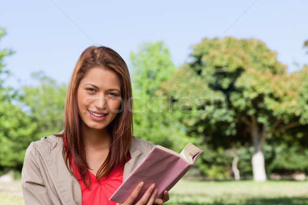 Woman grinning while looking straight ahead with a book in her hands in a sunny grassland area Stock photo © wavebreak_media