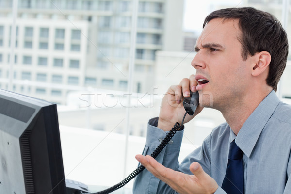 Confused office worker on the phone in his office Stock photo © wavebreak_media