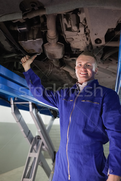 Smiling mechanic repairing with a spanner the below of a car in a garage Stock photo © wavebreak_media