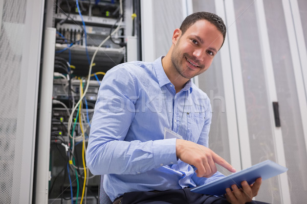 Happy technician working on tablet pc beside servers in data center Stock photo © wavebreak_media