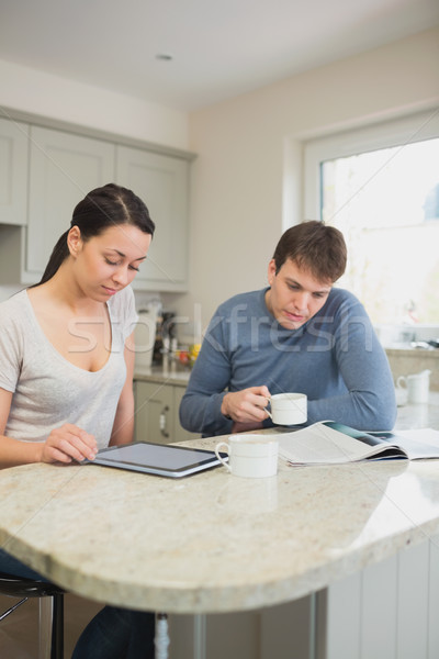 Two people reading from tablet pc and magazine in kitchen Stock photo © wavebreak_media