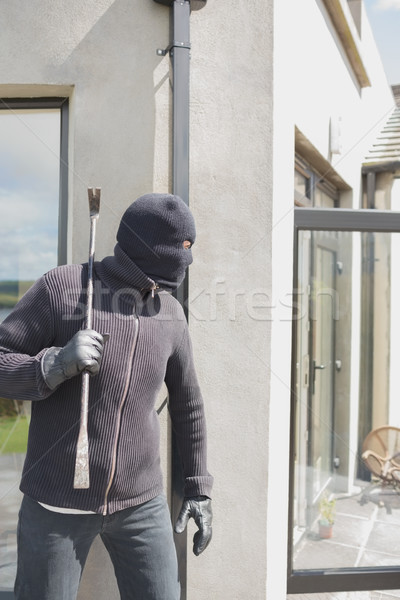 Robber hiding behind a wall with crow bar Stock photo © wavebreak_media