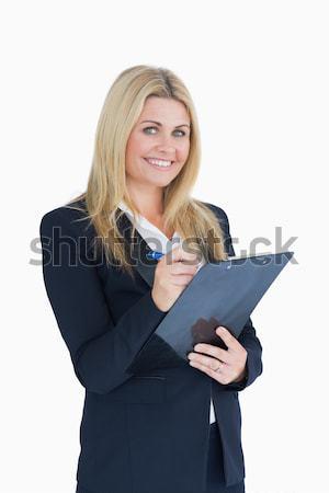 Business woman writing on clipboard on white background Stock photo © wavebreak_media