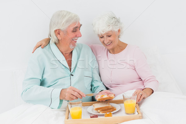 Smiling couple having breakfast in bed Stock photo © wavebreak_media