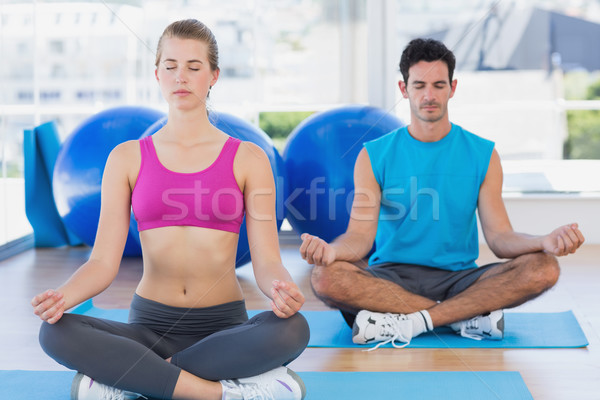 Couple sitting in lotus posture and eyes closed at fitness studi Stock photo © wavebreak_media