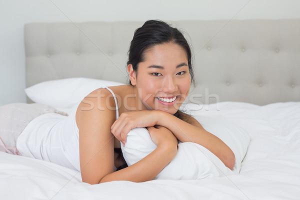 улыбаясь азиатских женщину кровать домой спальня Сток-фото © wavebreak_media