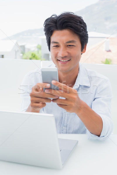 Feliz homem usando laptop telefone fora Foto stock © wavebreak_media