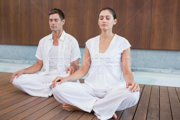 Attractive couple in white sitting in lotus pose Stock photo © wavebreak_media