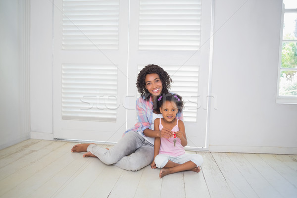 Mother and daughter sitting on the floor showing new house key Stock photo © wavebreak_media