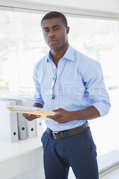 Komoly üzletember tart iratok néz kamera Stock fotó © wavebreak_media