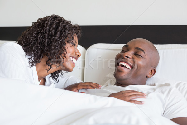 Happy couple cuddling in bed and laughing Stock photo © wavebreak_media
