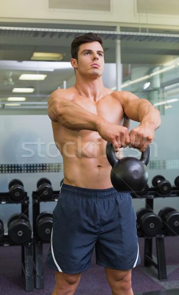 Muscular man lifting kettle bell in gym Stock photo © wavebreak_media