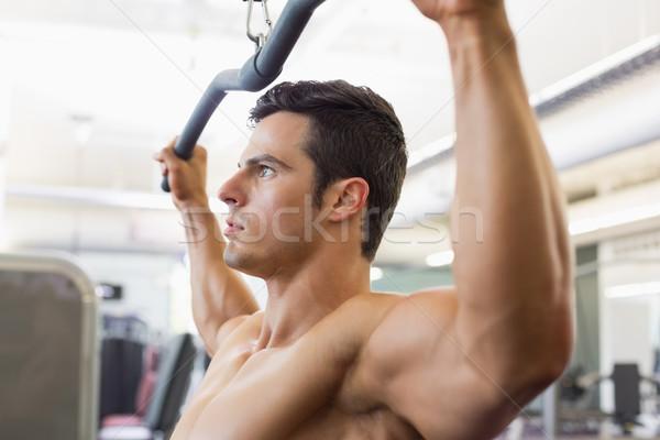 筋肉の 男 行使 マシン ジム 側面図 ストックフォト © wavebreak_media