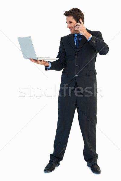 Businessman making a phone call while using a laptop Stock photo © wavebreak_media