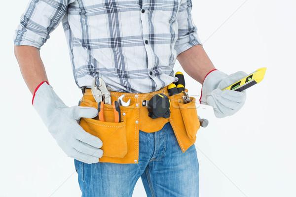 Technician holding spirit level over white background Stock photo © wavebreak_media