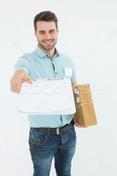 Delivery man with package giving clipboard for signature Stock photo © wavebreak_media