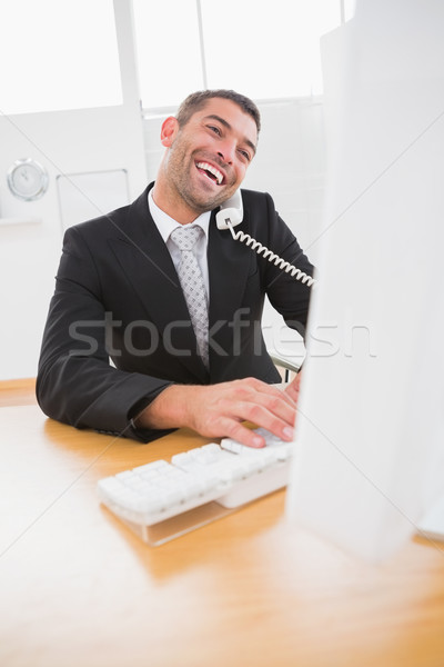 Smiling businessman working and phoning at his desk  Stock photo © wavebreak_media